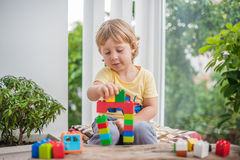 Cute little kid boy with playing with lots of colorful plastic blocks indoor. Active child having fun with building and creating o. F tower. Promotion of skills stock photos
