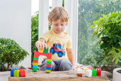 Cute little kid boy with playing with lots of colorful plastic blocks indoor. Active child having fun with building and creating o Royalty Free Stock Images