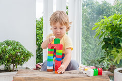 Cute little kid boy with playing with lots of colorful plastic blocks indoor. Active child having fun with building and creating o. F tower. Promotion of skills royalty free stock image
