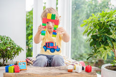 Cute little kid boy with playing with lots of colorful plastic blocks indoor. Active child having fun with building and creating o. F tower. Promotion of skills Royalty Free Stock Photos