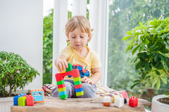 Cute little kid boy with playing with lots of colorful plastic blocks indoor. Active child having fun with building and creating o Royalty Free Stock Image