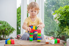 Cute little kid boy with playing with lots of colorful plastic blocks indoor. Active child having fun with building and creating o Stock Photography