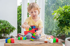 Cute little kid boy with playing with lots of colorful plastic blocks indoor. Active child having fun with building and creating o. F tower. Promotion of skills Stock Photography