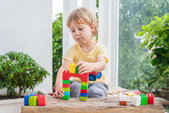 Cute little kid boy with playing with lots of colorful plastic blocks indoor. Active child having fun with building and creating o. F tower. Promotion of skills Royalty Free Stock Images