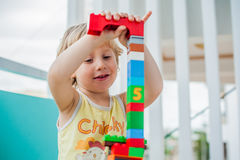 Cute little kid boy playing with lots of colorful plastic blocks indoor. Active child having fun with building and creating of tow. The boy makes eyes of Royalty Free Stock Image