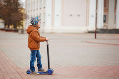 Cute little kid boy riding on scooter. Children actitvities outdoor in early spring. Royalty Free Stock Photography