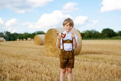 Cute little kid boy in traditional Bavarian costume in wheat field. German child with hay bale during Oktoberfest in Munich. Preschool boy play at hay bales royalty free stock photo
