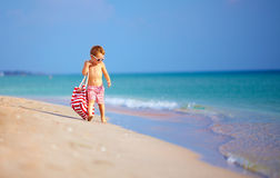 Cute little kid boy walking the seaside, summer holiday Stock Image