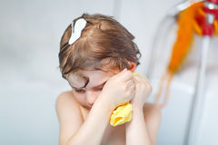 Cute little kid boy washing hair in bathtub Stock Images