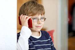 Cute little kid boy wearing eye glasses speaking on cellular phone. Adorable child holding smartphone and talking with a friend royalty free stock image