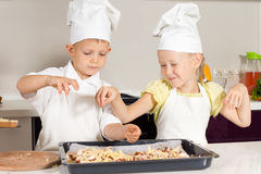 Cute Little Kid Chefs Putting Ingredients on Pizza Stock Images