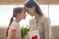 Cute little kid daughter congratulating happy mom with mothers day royalty free stock images