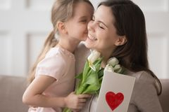 Kid daughter holding flowers kissing congratulating mom with mothers day. Cute little kid daughter holding spring flowers presenting greeting card congratulating stock photography