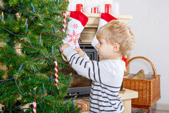 Cute little kid decorating Christmas tree, indoor Stock Photography
