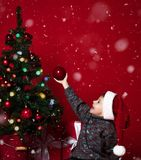 Cute little kid decorating Christmas tree with red beads stock image