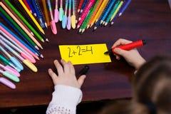 Cute little kid girl decide mathematics exercise stock image