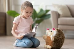 Cute little kid girl playing alone reading book to toy. Cute smart little kid girl playing alone reading story to fluffy hedgehog sitting on warm floor at home stock photos