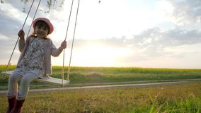 Cute little kid girl portrait sit on swing in nature sunset light background, happy little child have fun sway spin on. Swing, kid swaying nature in forest park stock video
