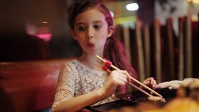 Little girl in a Japanese restaurant try the sushi rolls chopsticks. Cute little kid girl in restaurant funny try eating sushi with chinese chopsticks stock footage