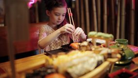 Cute little kid girl in restaurant funny try eating sushi with chinese chopsticks unsuccessful attempt stock footage