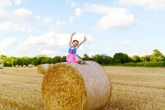 Cute little kid girl in traditional Bavarian costume in wheat field. German child with hay bale during Oktoberfest in Munich. Preschool girl play at hay bales royalty free stock photography