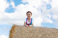 Cute little kid girl in traditional Bavarian costume in wheat field. German child with hay bale during Oktoberfest in Munich. Preschool girl play at hay bales stock image