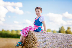 Cute little kid girl in traditional Bavarian costume in wheat field. German child with hay bale during Oktoberfest in Munich. Preschool girl play at hay bales royalty free stock image