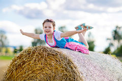 Cute little kid girl in traditional Bavarian costume in wheat field. German child with hay bale during Oktoberfest in Munich. Preschool girl play at hay bales stock images