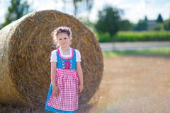 Cute little kid girl in traditional Bavarian costume in wheat field Stock Images