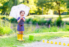 Cute little kid girl in yellow rainboots in summer park. Cute little kid girl in yellow rainboots playing with yellow rubber ducks in summer park. Creative royalty free stock images