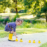 Cute little kid girl in yellow rainboots in summer park. Cute little kid girl in yellow rainboots playing with yellow rubber ducks in summer park. Creative stock images