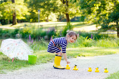 Cute little kid girl in yellow rainboots in summer park. Cute little kid girl in yellow rainboots playing with yellow rubber ducks in summer park. Creative stock image