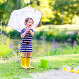 Cute little kid girl in yellow rainboots in summer park Stock Image