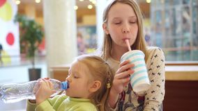 Cute little kid girls portrait funny eating in fast food court in a mall stock video