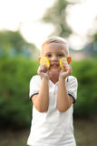 A cute little kid. Healthy and happy family. A young boy holding lemons on a green park background. Making lemonade. Stock Images