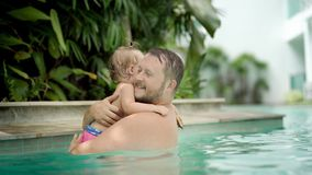 Cute little kid and his father having a swimming lesson in the pool. Father holds daughter in his arms and hugs. stock photo