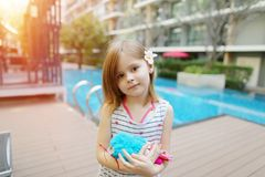 Cute little kid holding toy on background of swimming pool and apartment building Royalty Free Stock Photography