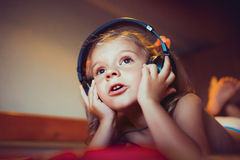 Cute little kid listening music lying on bed Royalty Free Stock Images