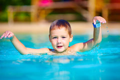 Cute little kid swimming in summer pool. Cute little kid swimming in outdoor pool Stock Images