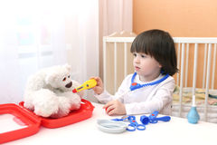 Cute little kid take bears temperature Royalty Free Stock Image