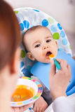 Cute little kid taking a bite of food Royalty Free Stock Photos