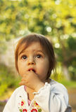 Cute little kid thinking in the park at summer day Royalty Free Stock Image