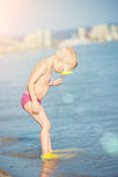Cute little kid wearing mask and flippers for diving at sand tropical beach. Stock Images