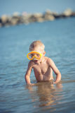 Cute little kid wearing mask and flippers for diving at sand tropical beach. Stock Photo