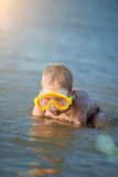 Cute little kid wearing mask and flippers for diving at sand tropical beach. Stock Image