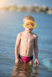 Cute little kid wearing mask and flippers for diving at sand tropical beach. Royalty Free Stock Image