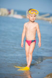 Cute little kid wearing mask and flippers for diving at sand tropical beach. Royalty Free Stock Photo