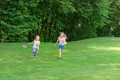 Cute little kids with badminton rackets running together. In park royalty free stock images