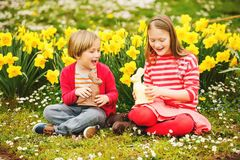 Little kids with chocolate bunnies, portrait. Cute little kids, big sister and small brother, with chocolate Easter bunnies celebrating traditional feast. Family Royalty Free Stock Photos