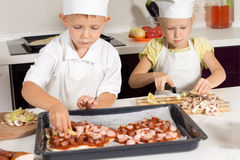 Cute Little Kids in Chef Attire Making Pizza Stock Images